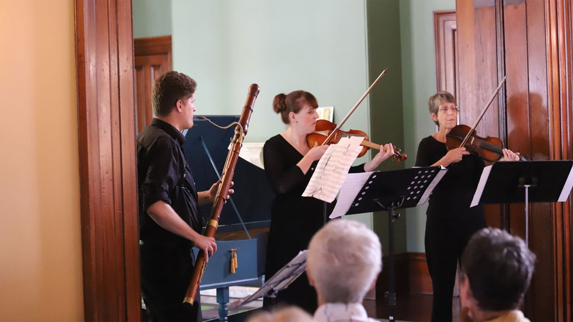 Three musicians playing inside Old Government House