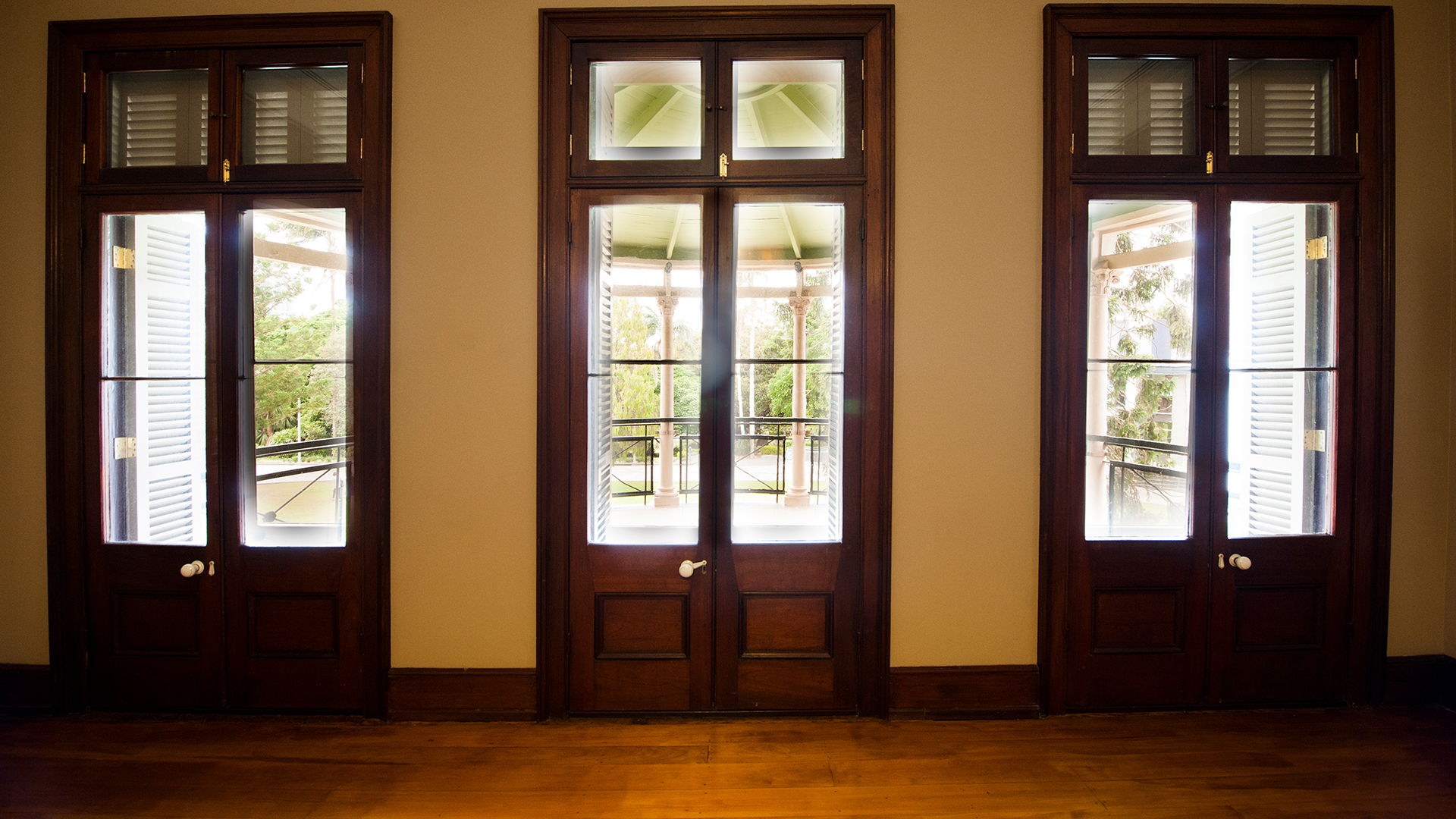 Indoor photo of Old Government House of 3 doors looking out to a covered, outdoor area