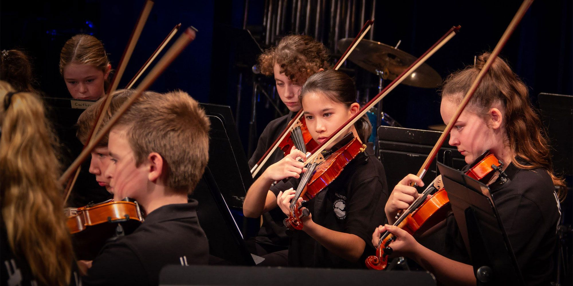 Young children playing string instruments in an orchestra