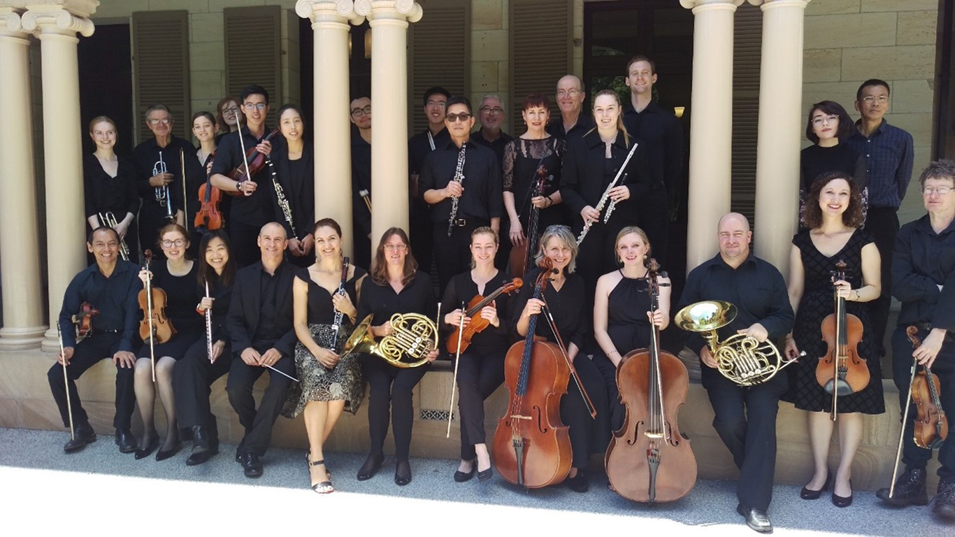 A group of 28 musicians posing for a group photo next to a sandstone building. Half of them are sitting and the other half are standing behind them. They are all holding their instruments