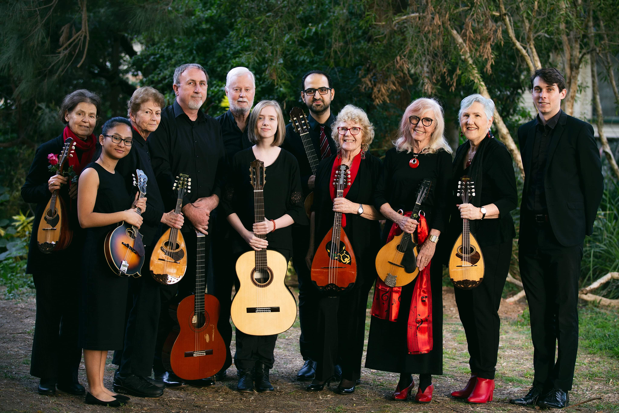 Photo of 11 musicians holding instruments standing in front of trees